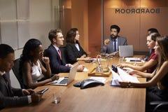 Collectieve bedrijfsmensen op een vergadering van de avondbestuurskamer Stock Fotografie