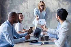 Collectieve bedrijfsteam en manager in een vergadering De leider deelt documenten aan collegaues uit stock fotografie