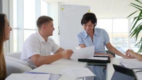 Collectieve uitvoerende holdingsvergadering met team van medewerkers bij lijst in modern bureau stock footage
