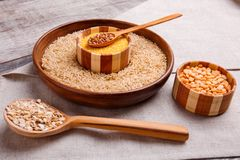 Collecting dry cereals. Buckwheat, rice, peas, oatmeal, wheat. On a gray table in a brown large plate with rice is a small wooden plate with wheat croup in a stock images