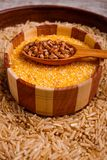 Collecting dry cereals. Buckwheat, rice, wheat in a large brown plate. In a large brown plate with rice there is a small wooden plate with yellow wheat grains stock photography