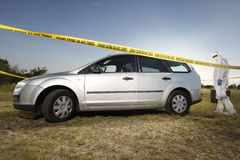 Collecting of evidences and traces by criminologist around car Royalty Free Stock Photography