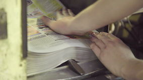Collecting of finished coloured newspapers after press in typography. stock footage