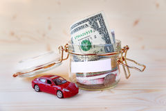 Collecting money for new car. Glass tin as moneybox with cash Stock Photo