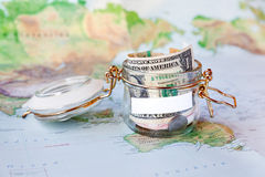 Collecting money for travel. Glass tin as moneybox with cash Stock Photos