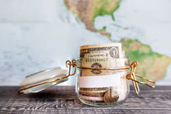 Collecting money for travel. Glass tin used as moneybox. Stock Images