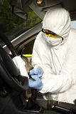 Collecting of odor traces by criminologist from driving wheel Royalty Free Stock Image
