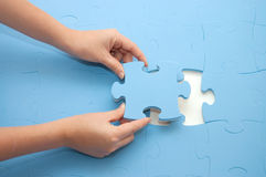Collecting a part of a puzzle Royalty Free Stock Photo