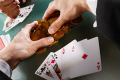 Collecting winning money. Cheating while playing poker with hidden Ace under the sleeve Royalty Free Stock Photography