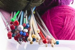 Collection of assorted knitting needles. Collection of assorted sizes of modern plastic knitting needles with colorful balls of magenta, purple and charcoal grey Stock Images