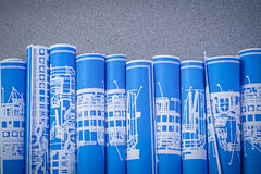 Collection of blue rolled up engineering drawings on grey backgr Stock Photo