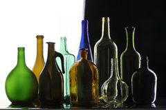 Collection bottles. Close-up collection of beautiful colored bottles of different shapes on a black and white background studio Royalty Free Stock Photos