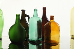 Collection bottles. Close-up collection of beautiful colored bottles of different shapes on a white background studio Royalty Free Stock Photo