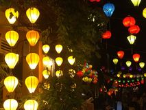 Colourful traditional Vietnamese lanterns lighting a street at night. A collection of bright lanterns at night. They are a range of colours, from yellow, red Stock Photos