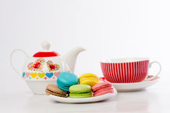 Collection of brightly colored French macarons on white background, lying in a saucer, standing next to the kettle Stock Images