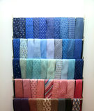 Collection of brightly-colored neck ties. On racks Royalty Free Stock Photos