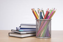 Collection of brightly colored pencil crayons. In a metal container on a wooden desk alongside a pile of school books or office journals Royalty Free Stock Photo
