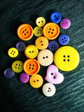 Big and small color buttons on black stock image