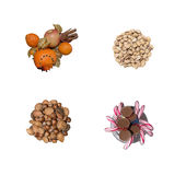 Collection of christmas goodies. Orange and apple fruits with cinnamon decoration, pistachio nuts in a heap, various mixed heap of nuts and chocolate candy stock photos