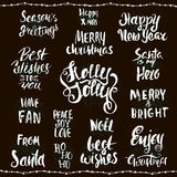 Collection of Christmas lettering on black background. Handwritten greetings. Royalty Free Stock Photography