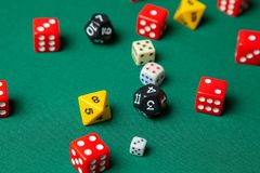 Collection of colored gaming dice cubes on green table royalty free stock photography