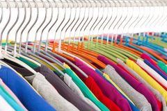 Collection of colored shirts on steel hangers Royalty Free Stock Images