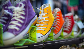 Collection of colorful casual gumshoes on shelves in fashion sto Stock Photo