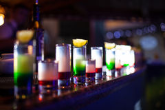 Collection of colorful shots with lemon on bar;. Set of alcohol mini cocktail shooters with lime Stock Photography