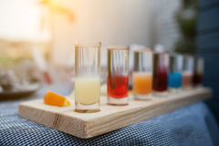 Collection of colorful shots on wooden table; Stock Photos
