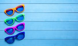 Collection of colorful sunglasses on blue wooden background Stock Image