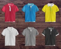 Collection of colorful t-shirts. On wooden background stock photos