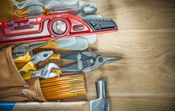Collection of construction tooling in building belt on wood boar Royalty Free Stock Photography