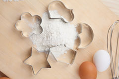 Collection of Cookie cutter forms around flour on wooden board Stock Images