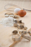 Collection of Cookie cutter forms around flour on wooden board Royalty Free Stock Photo
