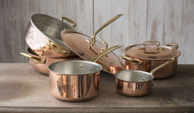A Collection of Copper Cookware. A set of copper cookware that include a small and medium-sized saucepan at front, a large saucepan, pot, and cover stacked on stock images