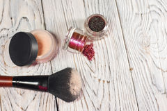 Collection of cosmetics for make-up artist. Powder, pigments, glitter, brushes and eyeliner. studio photo on a wooden background w Royalty Free Stock Photos
