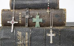 Close Up Antique and Modern Crosses on Antique Leather Bibles. Collection of crosses ranging from modern diamonds to ancient bronze on a stack of antique leather Royalty Free Stock Image