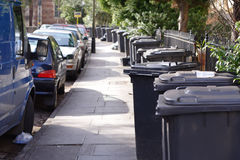 Collection day. Street full of dustbins awaiting collection royalty free stock image