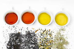 Collection de différents thés dans des tasses avec des feuilles de thé sur un fond blanc Image stock