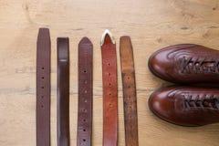 Collection de divers ceintures en cuir et shoues bruns sur un en bois Photos stock