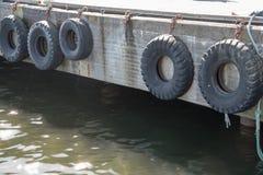 Collection de pneus sur les murs du bord de la mer pour éviter des bateaux et des bateaux se heurtant aux murs Photos libres de droits