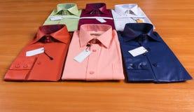 Collection des chemises habillées pliées des hommes avec des étiquettes Photographie stock libre de droits