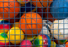 Collection of different balls in a metal cage. School gym Stock Image
