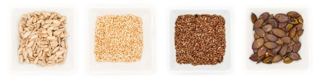 Collection of different edible seeds in white bowls royalty free stock photography