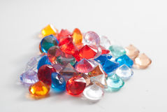 A collection of different faceted stones on a white background. The gems scattered on the table Stock Images