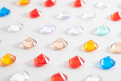 A collection of different faceted stones on a white background. Pattern of multicolored precious jewelry Stock Photo