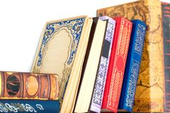 Collection of different old ornamental hardcover books on white. Collection of many different old ornamental hardcover books on white shelf. Indoors multicolored Royalty Free Stock Images