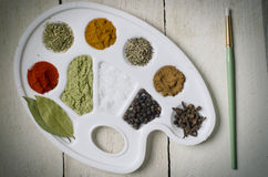 Collection of different spices on white plastic art palette, wooden background. Paint your food with spice. Stock Photos