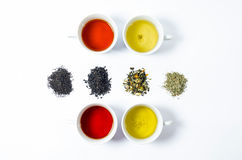 Collection of different teas in cups with tea leaves on a white background Royalty Free Stock Photography