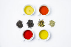 Collection of different teas in cups with tea leaves on a white background Stock Photos